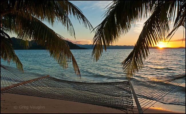 Hammock and palm trees on beach at sunset, Matangi Island, Fiji