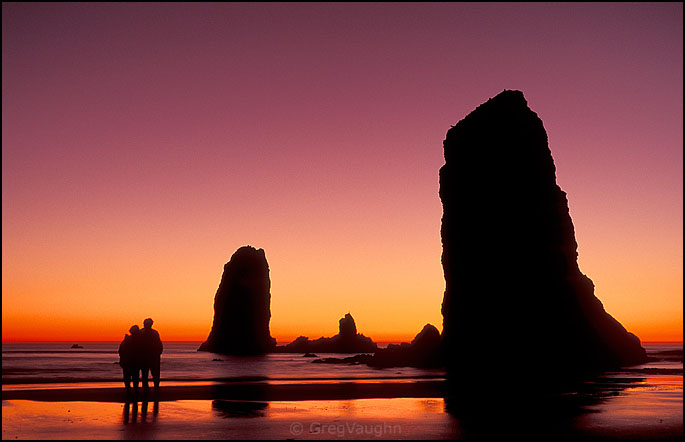 Couple watching sunset at the Needles at Cannon Beach on the Oregon coast.